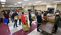 NWA Democrat-Gazette/BEN GOFF @NWABENGOFF<br /> Families and volunteers line up to collect meals Thursday, Nov. 28, 2019, during the annual Thanksgiving meal distribution at the First Baptist Church Olive Street campus in Rogers. <br /> <br /> Paul Olinger, a church member who helped coordinate the meal, said the event started 20 years ago 'As an outreach of the church to show the love of Christ in the community'. Volunteers from the church and the community cooked, packaged and delivered boxed meals that included ham, green beans, mashed potatoes and deserts. <br /> <br /> Open to anyone, a line wrapped around the room as families picked up boxes of food to take home, but Olinger estimates that 98 percent of the meals are delivered by volunteers.