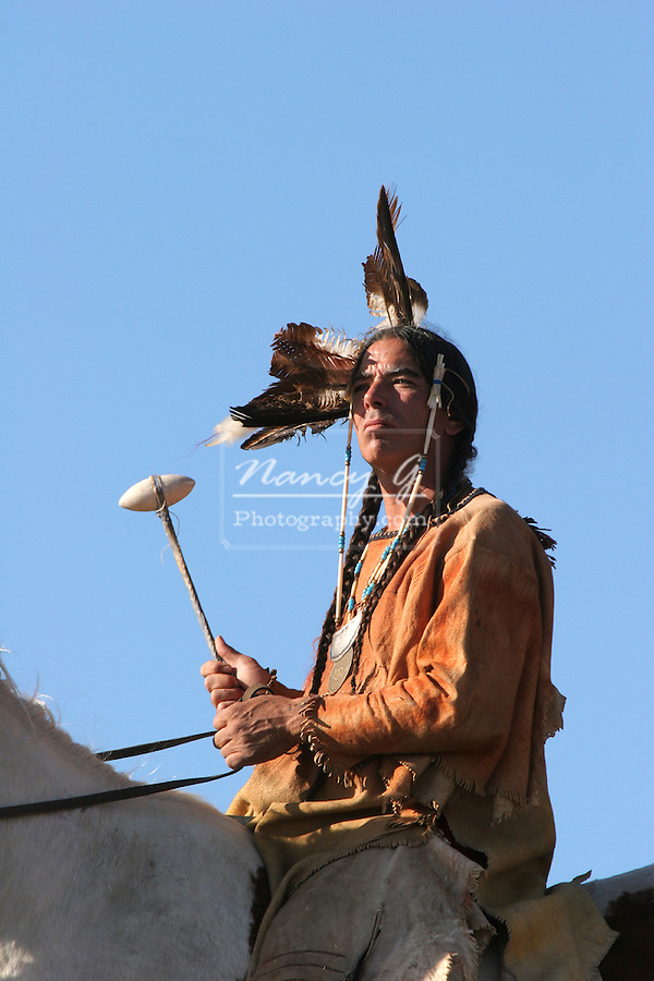 A Native American Indian man siting bareback on a horse riding the prairie with a weapon