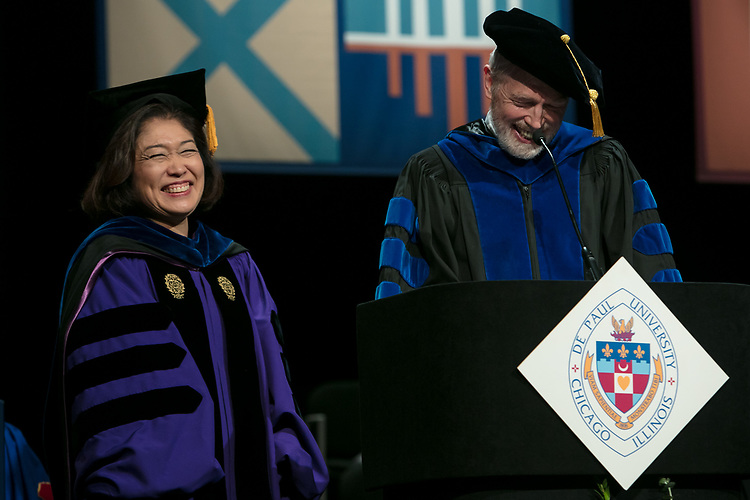 Judy Iwata Bundra, associate dean, left, receives a Via Sapientiae Award from Marten denBoer, provost, Saturday, June 10, 2017, during the DePaul University School of Music and The Theatre School commencement ceremony at the Rosemont Theatre in Rosemont, IL. (DePaul University/Jeff Carrion)