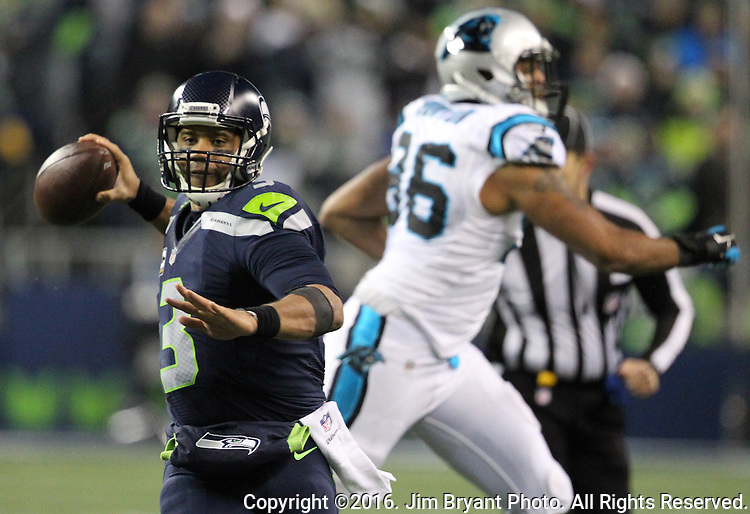 Seattle Seahawks quarterback Russell Wilson (3) scrambles away from Carolina Panthers defensive end Wes Horton (96) at CenturyLink Field in Seattle, Washington on December 4, 2016.  Wilson completed 26 of  36 passes for 277 yards and three for one touchdown and has one interception in the Seahawks 40-7 win over the Panthers.   ©2016. Jim Bryant photo. All Rights Reserved