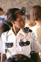 African American police woman age 28 helping out.  Youth Express Bicycle Safety Rodeo St Paul Minnesota USA