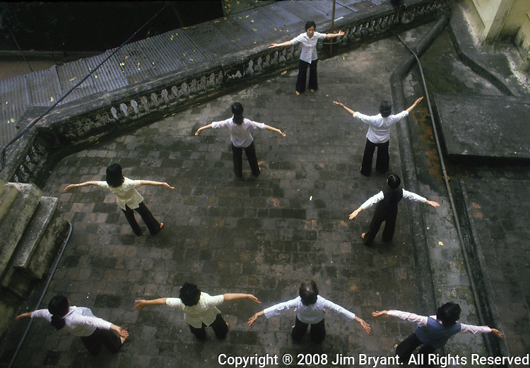 Thang Nhat Hotel workers perform morning exercises on a balcony overlooking the courtyard in Hanoi, North Vietnam.  (Jim Bryant Photo).....