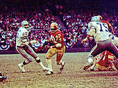 Washington Redskins running back Larry Brown (43) carries the ball and is pursued by left defensive end Tody Smith (85) and left defensive tackle Jethro Pugh (75) during the NFC Championship game against the Dallas Cowboys at RFK Stadium in Washington, DC on December 31, 1972.  The Redskins won the game and the right to play in Super Bowl VII by a score of 26 - 3.<br /> Credit: Arnie Sachs / CNP