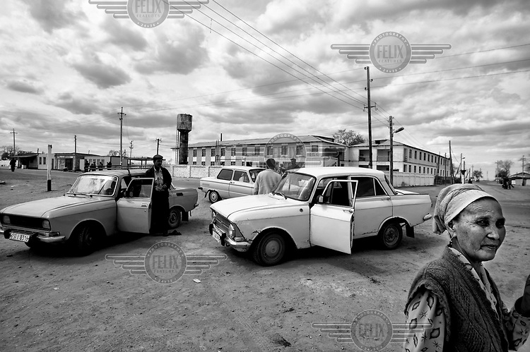 Drivers and their Soviet era cars in the town centre. During the 1950s and the 1960s the rivers that feed the Aral Sea (the Amu Darya and the Syr Darya) were diverted for irrigating cotton and other crops. This caused the lake to shrink uncovering sediments heavily polluted with industrial fertilizers that were washed into the lake over the preceding decades. Without the lake's water to contain it these toxic particles were spread by the wind and have caused numerous health problems in surrounding communities. Furthermore, as the lake evaporated the remaining water became increasingly saline and unable to sustain life, destroying the fishing industry. Muynak, once a thriving fishing port, became a depressed and dusty town far from the receding shore.