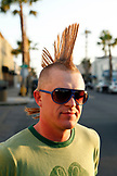 USA, California, San Diego, man walking near Ocean Beach stops and smiles sporting a large mohawk