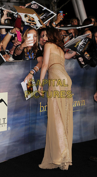 "Kristen Stewart (wearing Zuhair Murad Fall 2012).""The Twilight Saga: Breaking Dawn - Part 2"" Los Angeles Premiere held at Nokia Theatre L.A. Live, Los Angeles, California, USA..November 12th, 2012.full length beige nude corseted corset strapless gown lace chiffon panelling dress see through thru pink fans crowd signing autographs back behind rear side profile bending leaning posing picture photograph  profile .CAP/ROT/TM.©Tony Michaels/Roth Stock/Capital Pictures"