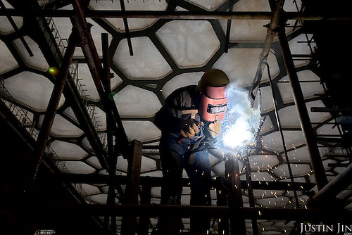 A welder contructs the dive platform at the Water Cube in Beijing, which is getting ready to host the 2008 Olympics. The Water Cube is where the swimming events will take place.