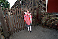 Little schoolgirl left standing outside the locked school gates waiting for her parents to pick her up and take her home. All the rest of the children have gone and she is all alone. This image may only be used to portray the subject in a positive manner..©shoutpictures.com..john@shoutpictures.com