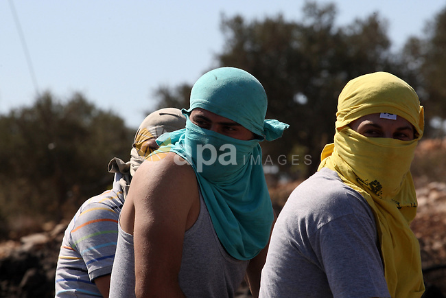 Masked Palestinian protesters watch Israeli soldiers (not pictured) during clashes over the Jewish settlement of Qadomem at Kofr Qadom village, near West Bank city of Nablus, 19 September 2014. Palestinians are repeatedly protesting at the site against Jewish settlements in the area. Photo by Nedal Eshtayah