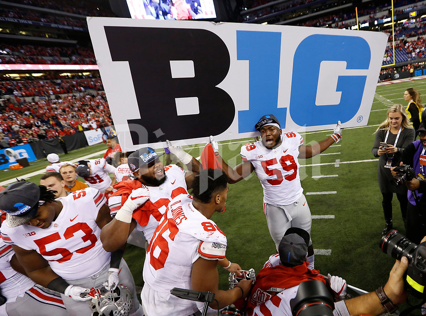 Ohio State Buckeyes defensive lineman Tyquan Lewis (59) holds a B1G sign following the Buckeyes' 27-21 win over the Wisconsin Badgers in the Big Ten championship football game at Lucas Oil Stadium in Indianapolis on Dec. 2, 2017. [Adam Cairns / Dispatch]