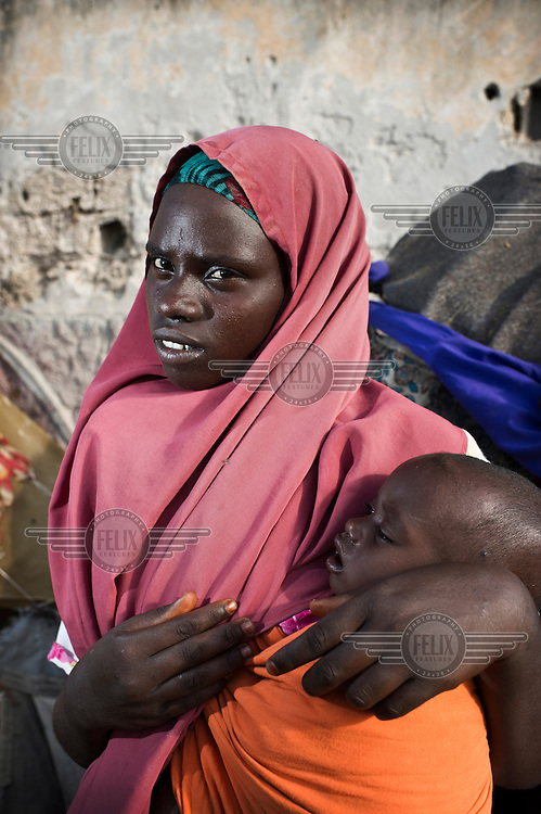 A woman holds her child at an IDP (internally displaced persons) camp in Mogadishu. The people staying here fled famine in South Somalia.