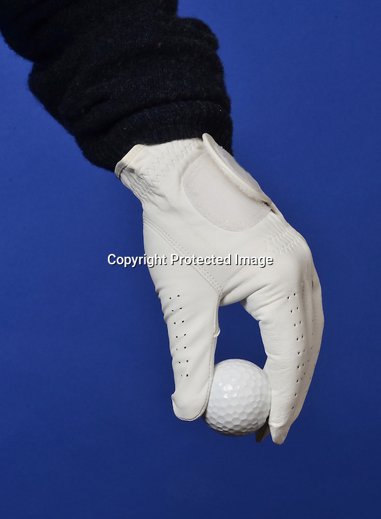 Stock photo of gloved hand holding golf ball