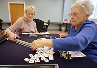 NWA Democrat-Gazette/DAVID GOTTSCHALK Alice Boepple (right) leans to bring more tiles into  play as she instructs Brenda Crum Monday, March 12, 2018, during a Mah Jongg lesson at the Rogers Adult Wellness Center. Organized games of Mah Jongg are played weekly on Mondays and Wednesdays. Lessons are available before play on Mondays. Mah Jongg is a tile-based game that was developed in China.