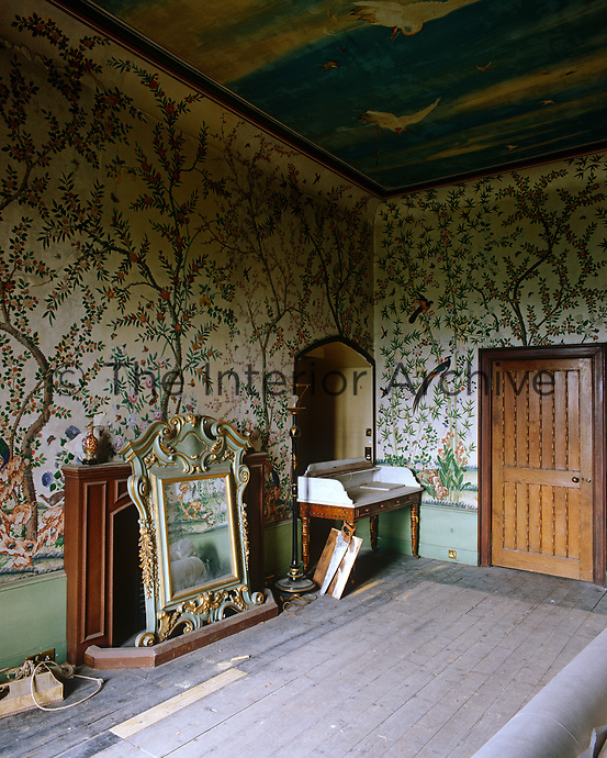 The walls of this empty attic room are covered in a Chinoiserie wallpaper and the ceiling has been painted with a naive mural