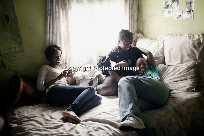 CAPE TOWN, SOUTH AFRICA - OCTOBER 19: Brenda Tahabatha (l) chats with friends on the bed in her bedroom in her house on October 19, 2011 in Khayelitsha outside Cape Town, South Africa. Cape Town is a city known for tolerating gays and lesbians except in the townships where they get harassed and often attacked. Some women have been raped in so called corrective rape, where men rapes them to make them women again. They can't show their love freely on the streets in the townships so they usually have to meet in houses and this bar.  (Photo by Per-Anders Pettersson)