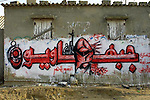 "A calligraphic mural from the Popular Front for the Liberation of Palestine (PFLP) which use draws in the letters is seen in Dir el Balah, Gaza. A masked man and a grenade are seen in the word ""Frontiest"" or ""people from the Front"". Photo by Quique Kierszenbaum"