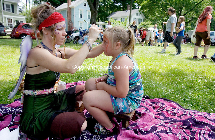 THOMASTON CT. 22 June 2013-062213SV09-Heidi Olsen of Harwinton paints a rainbow on the face of Genevieve Lizotte, 7, of Plymouth during the annual ArtzFest downtown Thomaston Saturday.<br /> Steven Valenti Republican-American