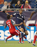 New England Revolution defender Darrius Barnes (25) passes the ball under pressure. In a Major League Soccer (MLS) match, the New England Revolution tied Toronto FC, 0-0, at Gillette Stadium on June 15, 2011.