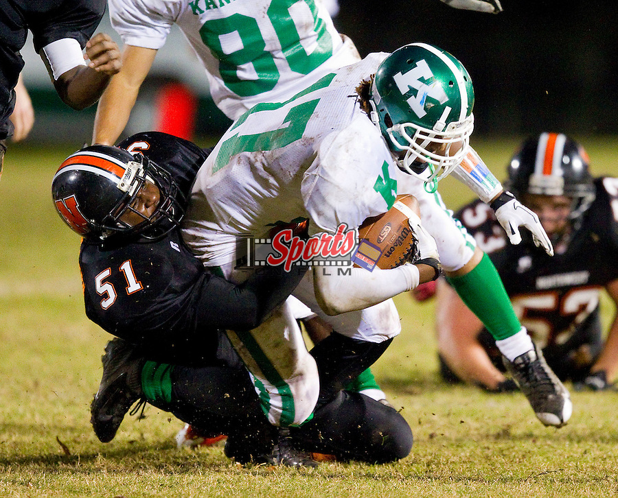 Kalif Phillips (17) of the A.L. Brown Wonders is tackled by Gary Whitaker (51) of the Northwest Cabarrus Trojans at Trojan Stadium October 21, 2011, in Concord, North Carolina.  The Wonders defeated the Trojans 44-7.  (Brian Westerholt/Sports On Film)