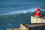 6th January 2018, Praia do Norte, Nazaré , Portugal; Alex Botelho catches a wave in front of the Faro in Praia do Norte, Nazaré