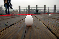 People gather during a snow squall at the South Street Seaport in New York on Friday, March 20, 2009 to welcome spring by standing eggs on end.  At the precise moment of the spring equinox, 7:44 AM, a raw egg can be  stood on its end bringing good luck for the rest of the year.  Urban shaman Donna Henes has been organizing this event for 34 years.  (© Frances M. Roberts)