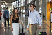 Real Austin business couple smiling while waiting to catch flight at the Austin–Bergstrom International Airport (ABIA) terminal.