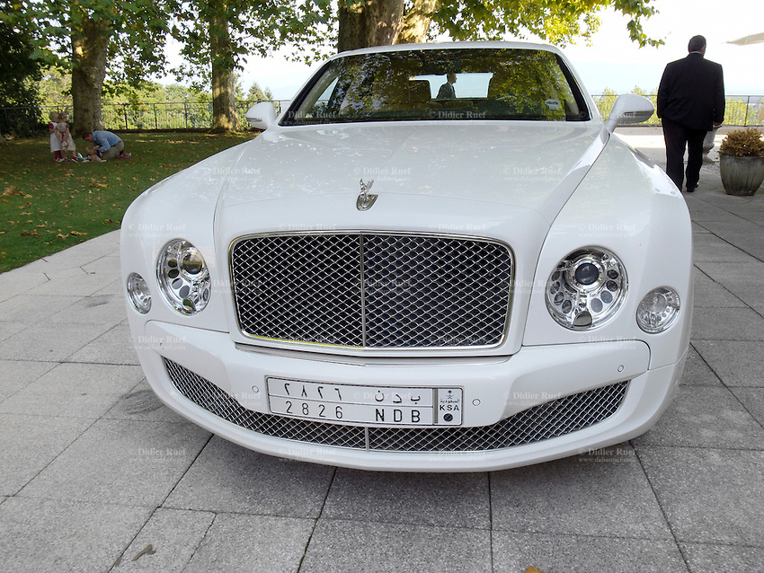 France. Ain department. Divonne. A white Bentley Mulsanne from the Kingdom of Saudi Arabia with two bodyguards in the garden of the hotel Chateau de Divonne. A father is changing the diapers on his youngest child while his two daughters are looking at him. 15.09.12 © 2012 Didier Ruef