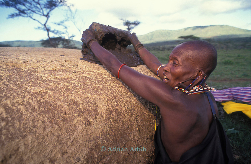 A Maasai woman covers her hut with cow dung.<br /> This has the effect of waterproofing  the roof .<br /> A moran manyatta, Kajiado, Kenya.