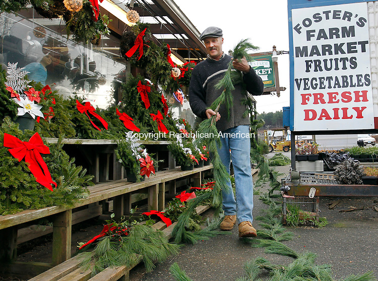 Thomaston, CT-30 November 2011-112911CM01-  Mark Foster of Foster's Farm Market puts together pine roping outside his store in Thomaston Tuesday afternoon.  The roping, which is used for holiday decoration is one of the many items Foster was getting ready for the season.  Also on display were wreaths, kissing balls and cemetery boxes.  Christopher Massa Republican-American