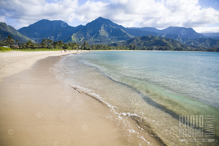 Clear blue water and small shorebreak at Hanalei Bay, with Namolokama Mountain in the background