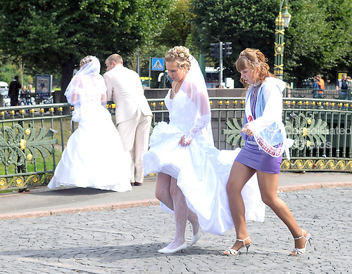 St. Petersburg, Russia - August 15, 2009 -- Two wedding parties pass along a bridge near the Church of Our Savior on the Spilled Blood in St. Petersburg, Russia on Saturday, August 15, 2009. Both brides had been posing for photos.  The bride in the foreground was returning to the rest of the wedding party, while the couple in the background was enjoying a short moment alone before returning to the rest of the wedding party..Credit: Ron Sachs / CNP