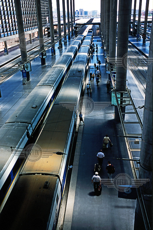 Passengers board a train preparing to depart from a platform at Madrid's Atocha railway station..