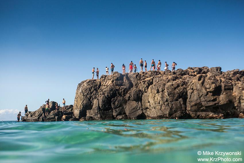 Beachgoers standing on top of the famous jump rock at Waimea Bay, Oahu