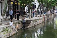 Suzhou, Jiangsu, China.  Visitors Walking along Canal Passing through Tongli Ancient Town near Suzhou.  A popular weekend tourist destination.