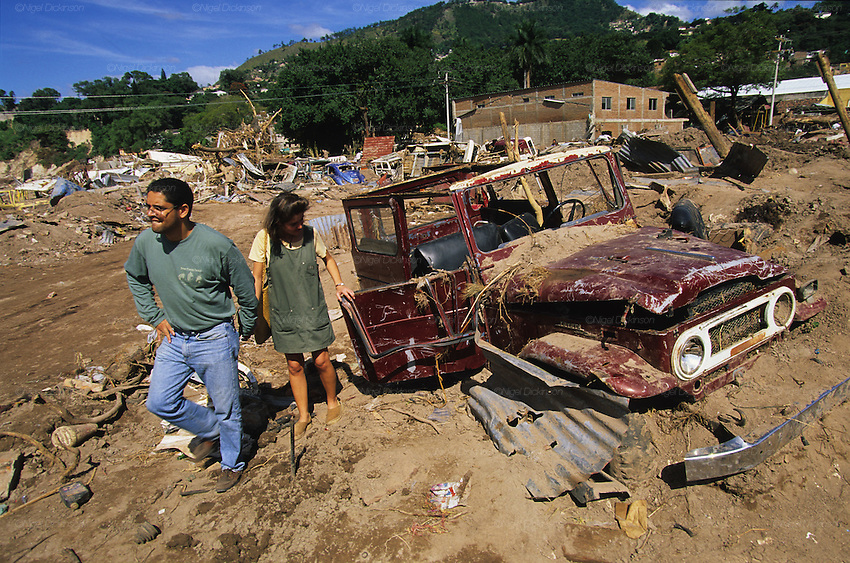 Central America, Honduras, Tegucigalpa. Couple and buried car under mud. Devastation in the aftermath of Hurricane Mitch. High winds and flooding. Infrastructure destroyed. Car park full of mud and debris.