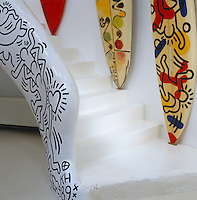 Detail of the curved staircase balustrade decorated by Keith Haring with a trio of surf boards resting on the steps, each painted by different artists inside Niki de Saint Phalle's sculptural house