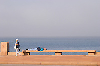 A woman walking on the pavement holding a thermos hot water flask with mate herbal tea and a man lying on a bench sleeping, on the riverside seaside walk along the river Rio de la Plata Ramblas Sur, Gran Bretagna and Republica Argentina Montevideo, Uruguay, South America