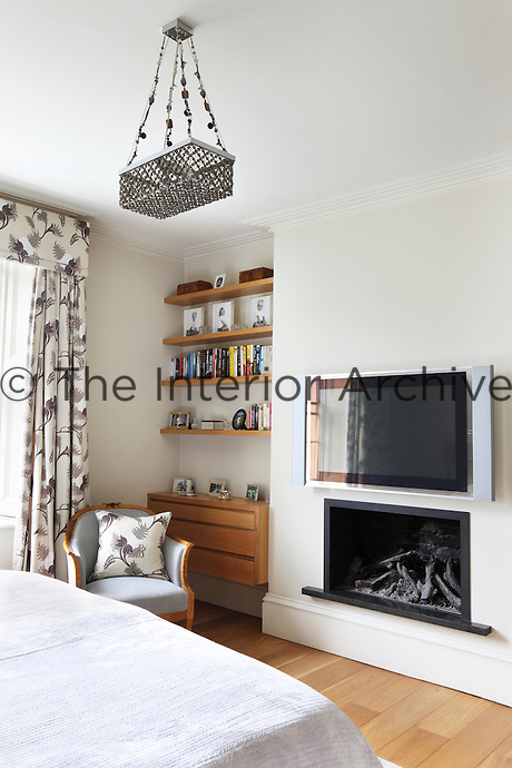 A bedroom with matching floral soft furnishings and built-in shelving