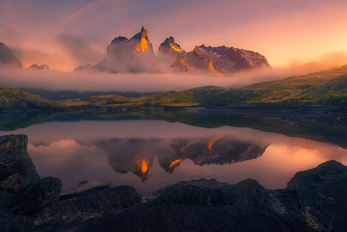 Los Cuernos del Paine peeks through low clouds and fog, illuminated by the rising sun.  Just moments later, a heavy fog came through as the scene vanished into the light of day.