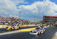 Jul, 22, 2012; Morrison, CO, USA: NHRA funny car driver Courtney Force (near lane) races alongside Ron Capps during the Mile High Nationals at Bandimere Speedway. Mandatory Credit: Mark J. Rebilas-