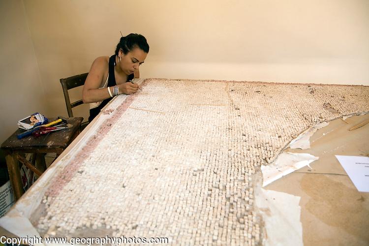 Woman curator repairing mosaic, Archaeological museum, Rhodes, Greece