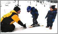 A young child/toddler has his first lesson in snow skiing. Father teaches boys how to ski. Photo taken in Pennsylvania. Model released image.