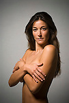 Topless woman with arms crossing over her breasts