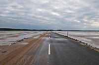 Sand covered road to Lindisfarne - Holy island at low tide, Lindisfarne, England.  The road is only passable for a few hours around low tide, tidal charts are posted listing opening times