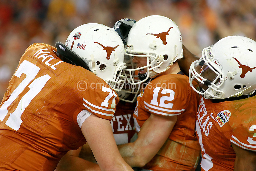 Jan 05, 2009; Glendale, AZ, USA; Texas Longhorns quarterback Colt McCoy (12) is congratulated by teammates after a touchdown run in the third quarter of the Fiesta Bowl against the Ohio State Buckeyes at University of Phoenix Stadium.  The Longhorns won the game 24-21.