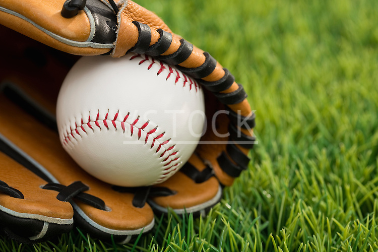 Ball inside catchers mitt on grass