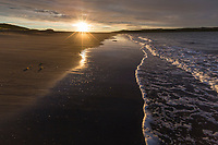 Sun rise over the waves along the shore of a sandy beach in Katmai National Park, Alaska Peninsula, southwest Alaska.