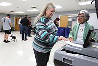 NWA Democrat-Gazette/DAVID GOTTSCHALK  Brenda Taylor (right), a poll sheriff, assists Dianna Eldridge Tuesday, November 5, 2019, as she casts her ballot in the 2019 Bentonville Annual School Election inside the Activity Center at the Bentonville Church of Christ.
