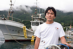 Businessman Kenichiro Yagi stands by fishing boats on the quay near his business in Ofunato, Iwate Prefecture, Japan on 05 Sept., 2011. Photograph: Robert Gilhooly