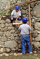 Peru, Machu Picchu.   Historic Preservation.  Workers Reconstructing Walls from Original Collapsed Stones. Numbered Stones suggest the study required before this work could be accomplished.